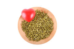 Raw pumpkin seeds on wooden plate heart shape isolated on white Stock Photo
