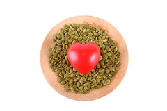 Raw pumpkin seeds on wooden plate heart shape isolated on white Stock Photos