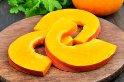 Raw pumpkin slices on cutting board Royalty Free Stock Photos