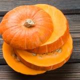 Raw pumpkin slices on the dark table Royalty Free Stock Photos