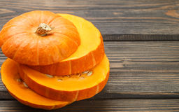 Raw pumpkin slices on the dark table Stock Image