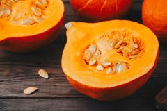 Raw pumpkin slices with seeds on a wooden background. Fresh raw pumpkin slices with seeds on a wooden background Stock Images
