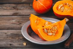 Raw pumpkin slices with seeds on a wooden background. Fresh raw pumpkin slices with seeds on a wooden background Stock Photo