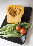 Raw Pumpkin and tomatoes with sorrel. Pumpkin on cutting board with tomatoes and sorrel Stock Photography