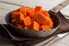 Raw pumpkin on wooden background. Fresh raw pumpkin in bowl on wooden background. Selective focus Stock Images