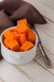 Raw pumpkin on wooden background. Fresh raw pumpkin in bowl on wooden background. Selective focus Stock Photos