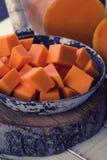 Raw pumpkin on wooden background. Fresh raw pumpkin in old frying pan on wooden background. Selective focus Stock Photos