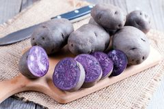 Raw purple potato. On old wooden background, close up royalty free stock photo