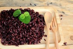 Raw purple rice berries and cooked of delicious for health. Royalty Free Stock Photography