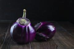 Raw  purple round eggplants. On dark rustic wooden background Stock Photos