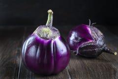 Raw purple round eggplants. On dark rustic wooden background Royalty Free Stock Photo