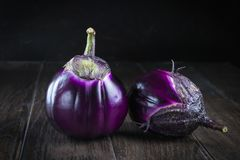 Raw  purple round eggplants. On dark rustic wooden background Stock Images
