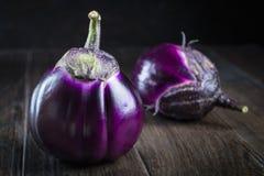 Raw  purple round eggplants. On dark rustic wooden background Stock Photo