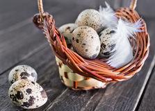 Raw quail eggs. In the basket and on a table Stock Photography
