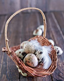 Raw quail eggs. In the basket and on a table Stock Image