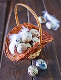 Raw quail eggs. In the basket and on a table Royalty Free Stock Photo