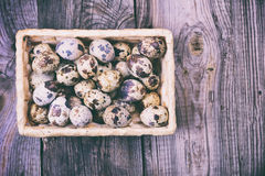 Raw quail eggs in a wicker basket, top view. Empty space on the right Stock Image
