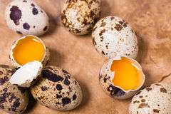 Raw quail eggs on the wooden background. With some open eggs Royalty Free Stock Photography