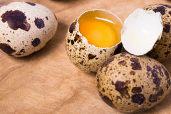 Raw quail eggs on the wooden background. With some open eggs Stock Image
