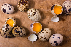 Raw quail eggs on the wooden background. With some open eggs Royalty Free Stock Images