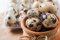 Raw quail eggs in a wooden bowl on burlap background. Raw quail eggs in a wooden bowl on a burlap background Royalty Free Stock Photography