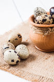 Raw quail eggs in a wooden bowl on burlap background Stock Photo