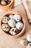 Raw quail eggs in a wooden bowl on burlap background. Raw quail eggs in a wooden bowl on a burlap background Royalty Free Stock Image