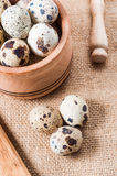 Raw quail eggs in a wooden bowl on burlap background. Raw quail eggs in a wooden bowl on a burlap background Royalty Free Stock Photo