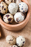 Raw quail eggs in a wooden bowl on burlap background Stock Images