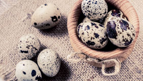 Raw quail eggs in a wooden bowl on burlap background. Raw quail eggs in a wooden bowl on a burlap background Stock Photo