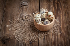 Raw quail eggs in a wooden bowl on wooden table. Selective focus Stock Photography