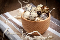Raw quail eggs in a wooden bowl on wooden table. Selective focus Stock Images