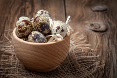 Raw quail eggs in a wooden bowl on wooden table. Selective focus Stock Photos