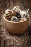 Raw quail eggs in a wooden bowl on wooden table. Stock Photography