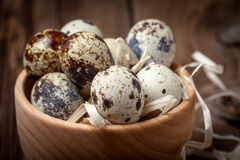 Raw quail eggs in a wooden bowl on wooden table. Selective focus Royalty Free Stock Photo