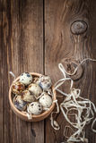 Raw quail eggs in a wooden bowl on wooden table. Stock Photo