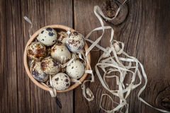 Raw quail eggs in a wooden bowl on wooden table. Selective focus Royalty Free Stock Photos