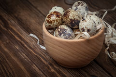 Raw quail eggs in a wooden bowl on wooden table. Selective focus Royalty Free Stock Images