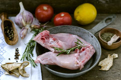 Raw rabbit legs and spices. On a wooden surface Stock Photo