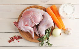 Raw rabbit on a wooden Board with ingredients for stewing milk, Royalty Free Stock Images