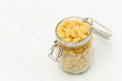 Raw radiatori pasta on a glass jar. On blue wood table Royalty Free Stock Photography