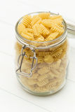 Raw radiatori pasta on a glass jar. On blue wood table Stock Photography