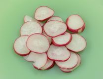 Raw radish slices. On green plate as ingredient to add during meal preparation Stock Image
