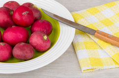 Raw radishes in glass plate and knife on napkin. Raw radishes in glass plate and knife on yellow napkin Royalty Free Stock Image