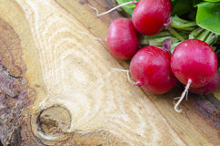 Raw radishes on a wooden board. Fresh natural radishes on a wooden board Stock Images