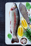 Raw rainbow trout. Close up of fresh raw rainbow trout on marble board with lemon, herbs and spices over dark rustic table, preparation. Top view of fish food Royalty Free Stock Images