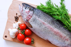 Raw rainbow trout on a cutting board with vegetables and spices Royalty Free Stock Image