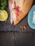 Raw rainbow trout fish on old wooden table. With lemon and spices, food background Stock Images
