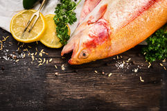 Raw rainbow trout fish preparation on old wooden table Royalty Free Stock Images