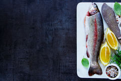 Raw rainbow trout. Fresh raw rainbow trout on marble board with lemon, herbs and spices over dark rustic table, preparation. Top view of fish food background Stock Photo